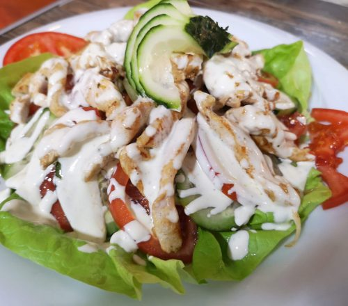 A chicked salad with cucumbers,lettuce leaves and tomato topped off with white ranch.
