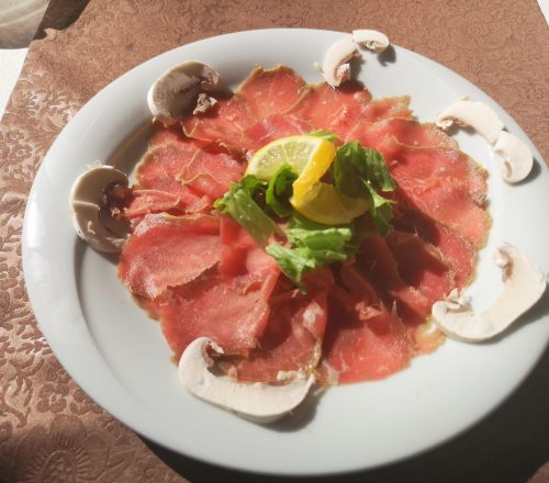 Prosciutto plate served on a white plate with mushrooms around it and a piece of lemon and lettuce on top.