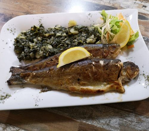 Two fried fish served with spinach and lemon.