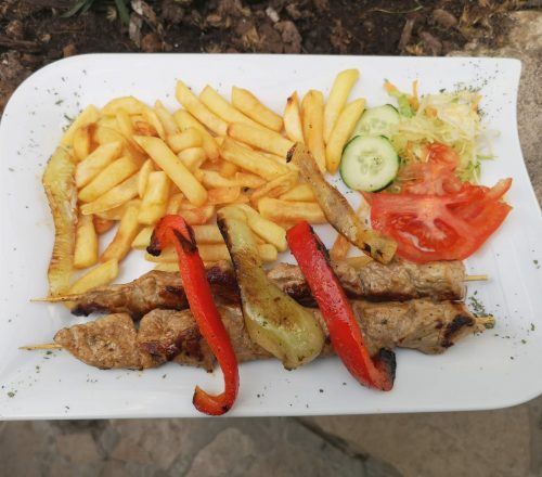 Skewers with fries on the side, lettuce, tomato and grilled peppers.