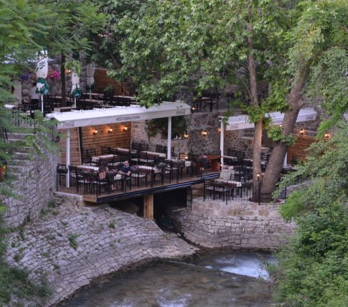 Restaurant terrace with a tree on side and a view on the river.