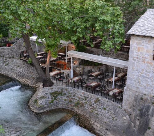 Restaurant terrace with a tree on side and a view on the river. Enclosed by cement walls built in old style.