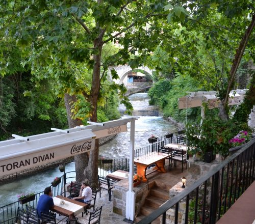 Restaurant terrace and outdoor seating with a view on the river and surrounding trees.