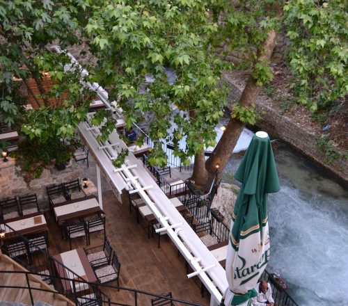 Restaurant terrace with table setting and the river flowing by it.